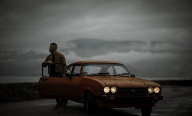 Gabriele (aka Gangalistics) stands behind the open door of an orange car. A grey sky looks over him.